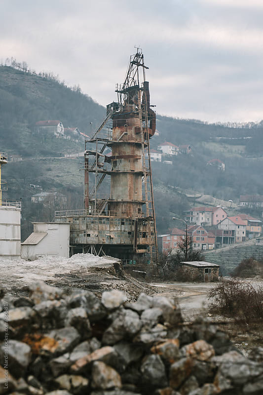 abandoned factory site with big steel tower in former war zone, kosovo by Leander Nardin for Stocksy United