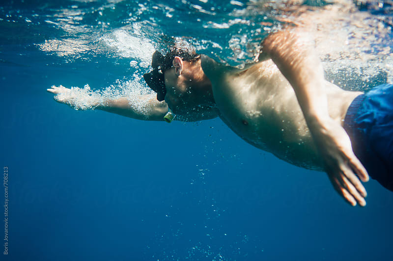 Man swimming in the ocean by Boris Jovanovic for Stocksy United