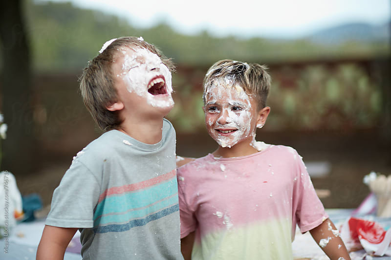 Funny moment of two friends in a birthday cake war by Miquel Llonch for Stocksy United