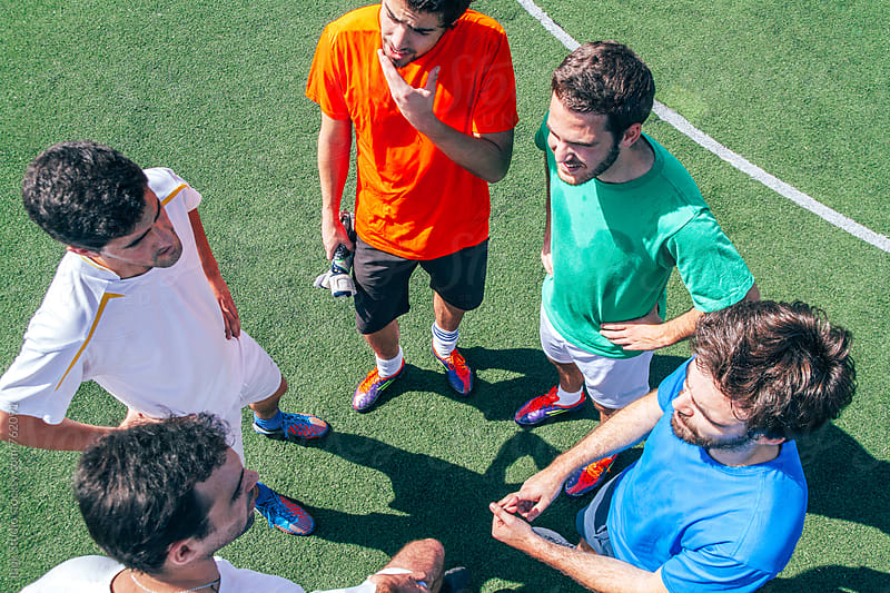 Soccer players talking between them in a soccer field - overhead by Inuk Studio for Stocksy United