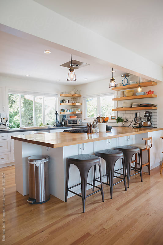 Bright modern kitchen with wood bar and open shelving by Rob and Julia Campbell for Stocksy United