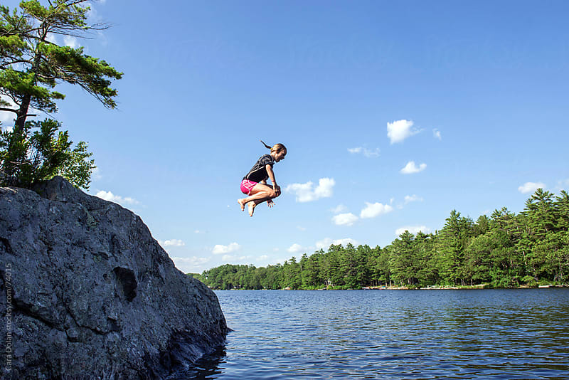 Girl does a cannonball jump off a rock into the lake by Cara Dolan for Stocksy United