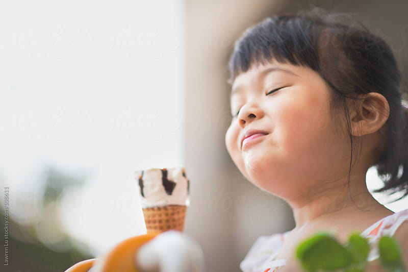 Kid closes eyes and enjoys ice cream by Lawren Lu for Stocksy United