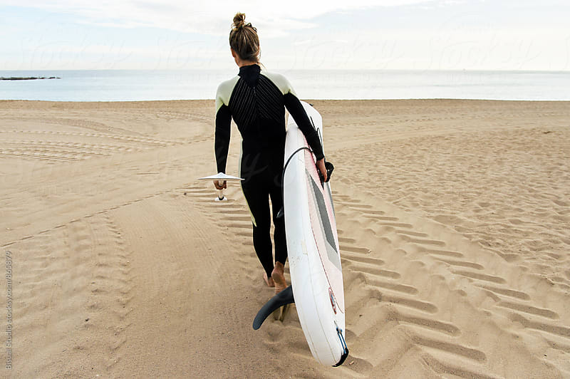 Blonde girl walking with her paddle board on the beach, Barcelona by Bisual Studio for Stocksy United