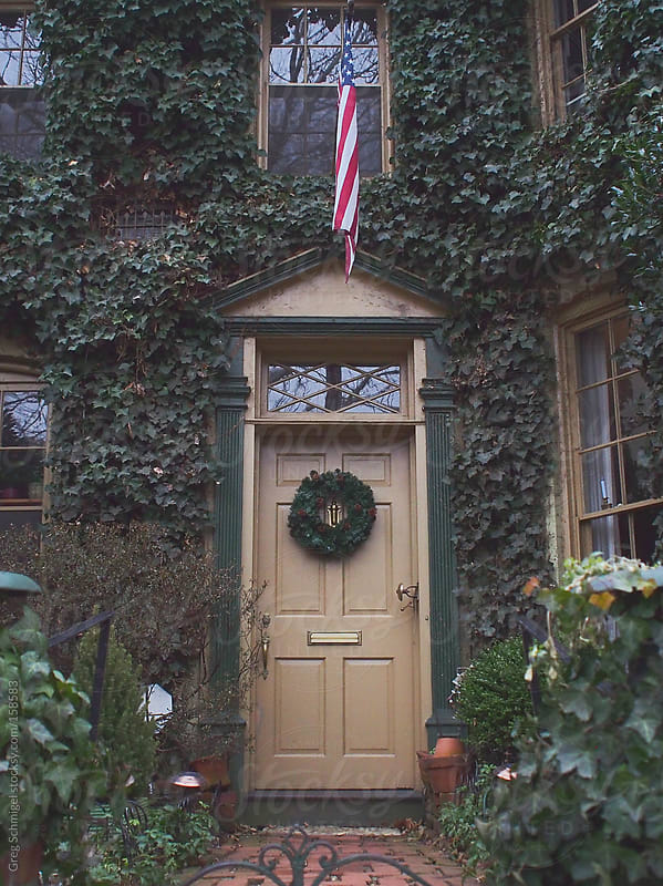 Door of house with wreath covered in ivy by Greg Schmigel for Stocksy United