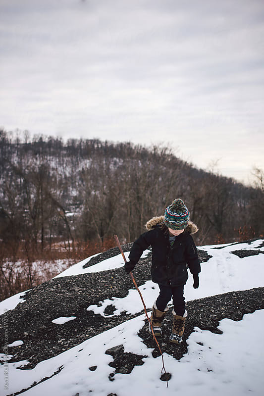 Young Boy Exploring Outdoors on a Rock by Kevin Keller for Stocksy United