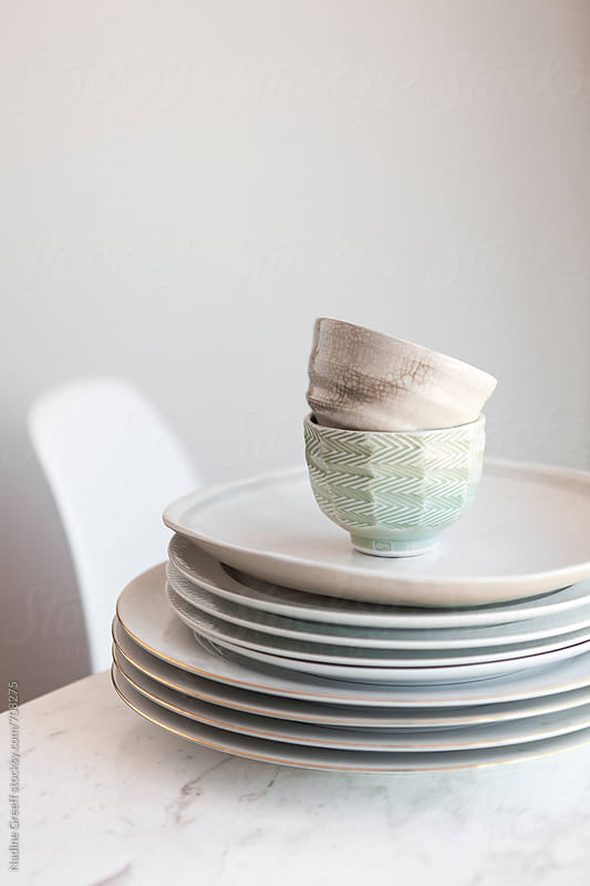 Pile of white plates and two kitchen bowls on marble countertop by Nadine Greeff for Stocksy United