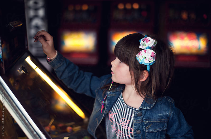 Little girl playing a penny slot machine by CHRISTINA K for Stocksy United
