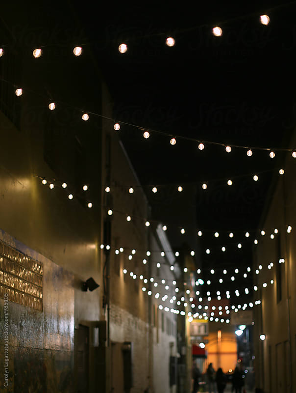 Quaint alleyway with bulb lights by Carolyn Lagattuta for Stocksy United