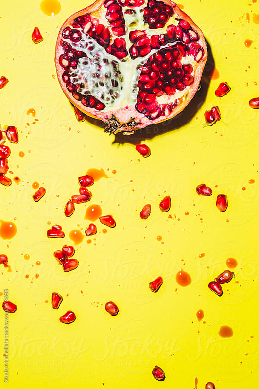 pomegranate on a yellow background by Juri Pozzi for Stocksy United