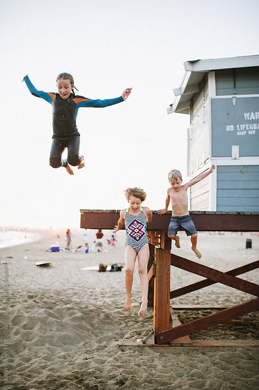 Kids jumping off lifeguard tower for fun by Kristin Rogers Photography for Stocksy United
