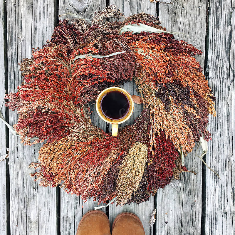 A cup of black coffee sits in the middle of an autumn wreath by Holly Clark for Stocksy United