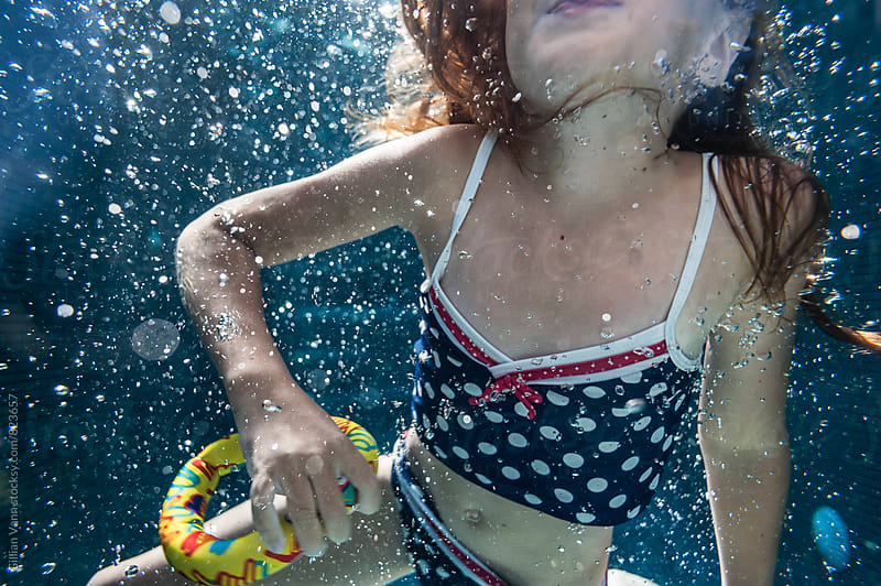 girl in swimming pool with bubbles by Gillian Vann for Stocksy United