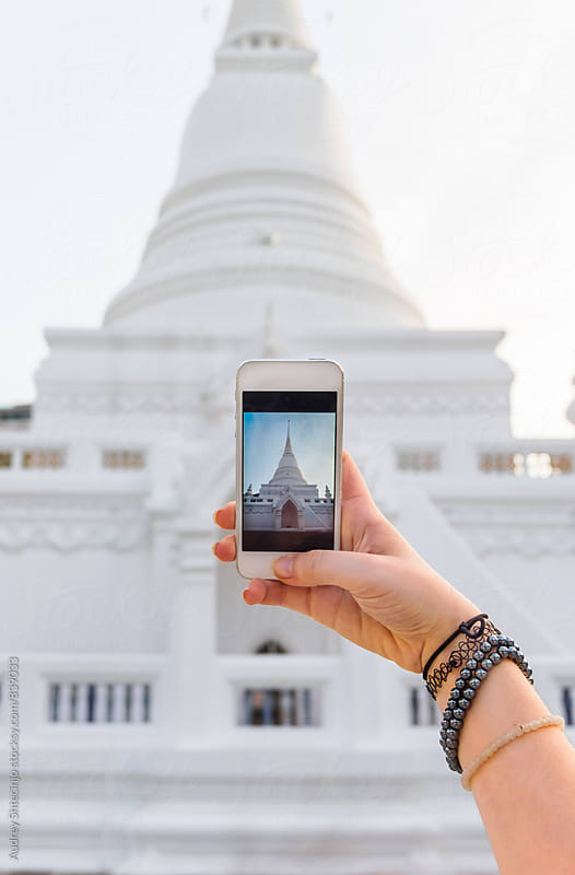 Hand with phone taking photo of Wat Patum /royal buddhist temple in Bangkok /Thailand by Audrey Shtecinjo for Stocksy United