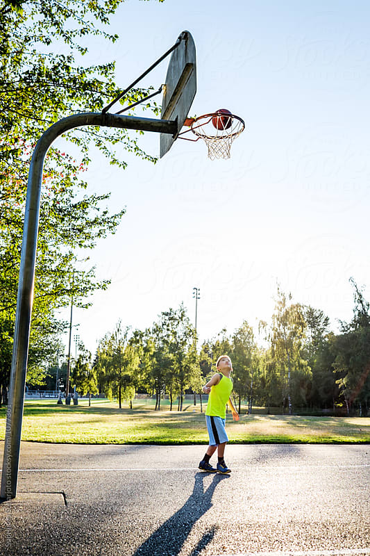 Asian kid shooting basketball in an outdoor basketball court by Suprijono Suharjoto for Stocksy United