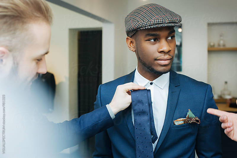 Men's Fashion - Portrait of Stylish Young Black Man Trying on Blue Tie by Julien L. Balmer for Stocksy United