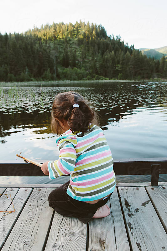 Two year old girl pretending to fish from a dock by Justin Mullet for Stocksy United