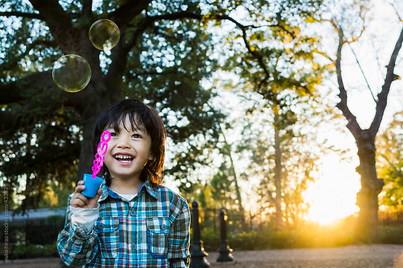 Asian little boy with bubbles at sunset by yuko hirao for Stocksy United