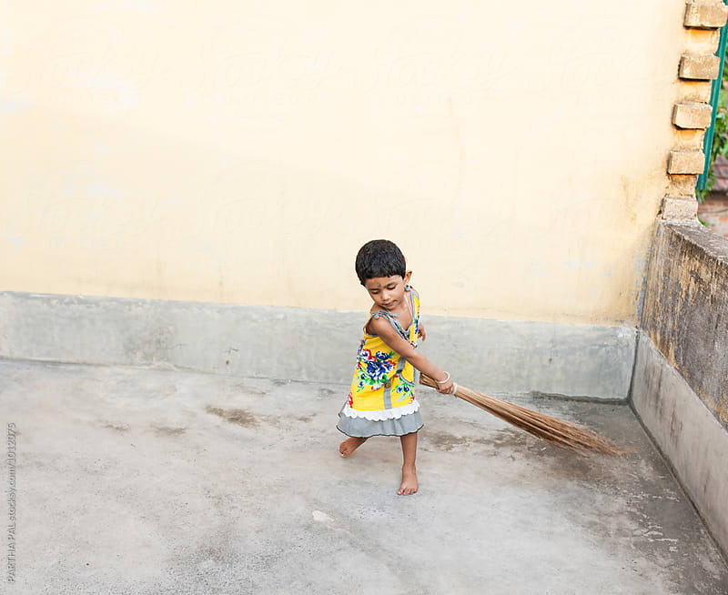 Little girl trying to sweep the floor in a playful mood by PARTHA PAL for Stocksy United