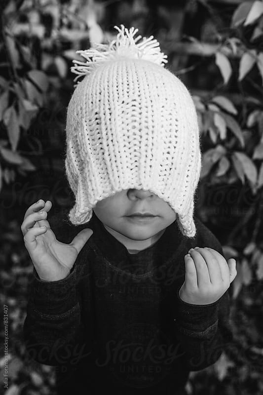 Little girl pulls a woolly hat over her eyes. by Julia Forsman for Stocksy United