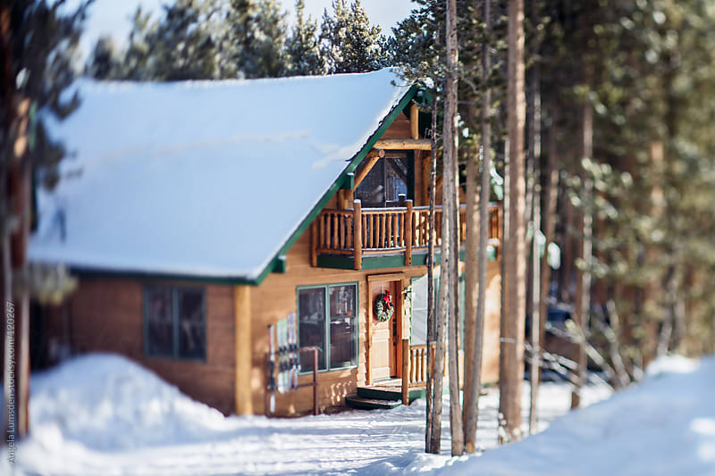 Snow covered cabin in a mountain forest by Angela Lumsden for Stocksy United
