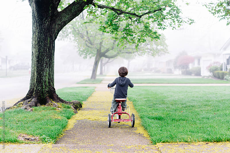 young boy rides tricycle down sidewalk by Maria Manco for Stocksy United