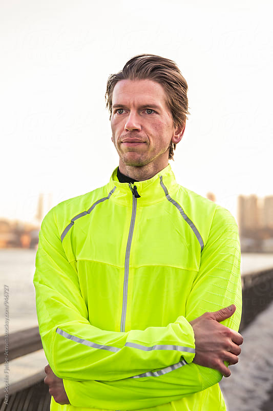 Male runner standing by East River by Ann-Sophie Fjelloe-Jensen for Stocksy United