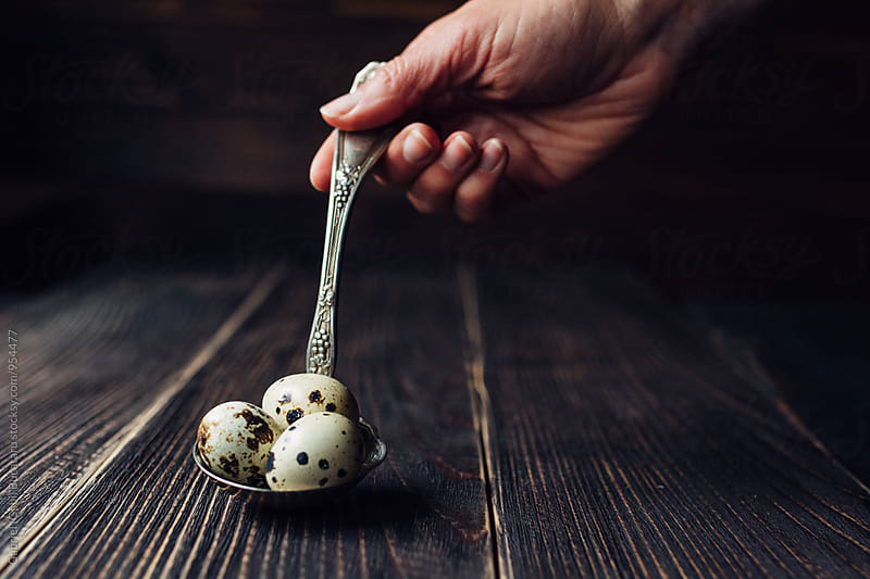 Woman's hand holding a spoon with quail eggs by Gabriel (Gabi) Bucataru for Stocksy United