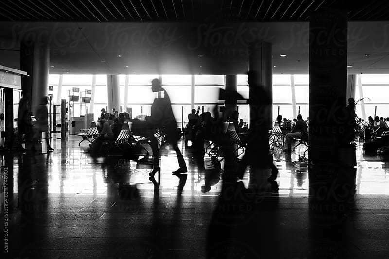 Black and white scene of people commuting in an airport by Leandro Crespi for Stocksy United