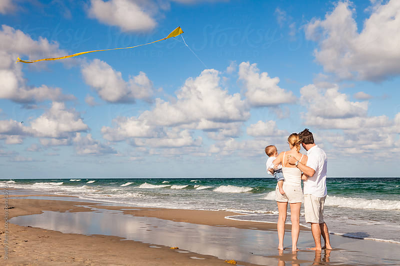 Happy Young Family of Three on a Beach by Shelly Perry for Stocksy United