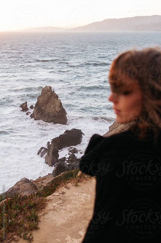 out of focus female at rocky coast line during sunset by Jesse Morrow for Stocksy United