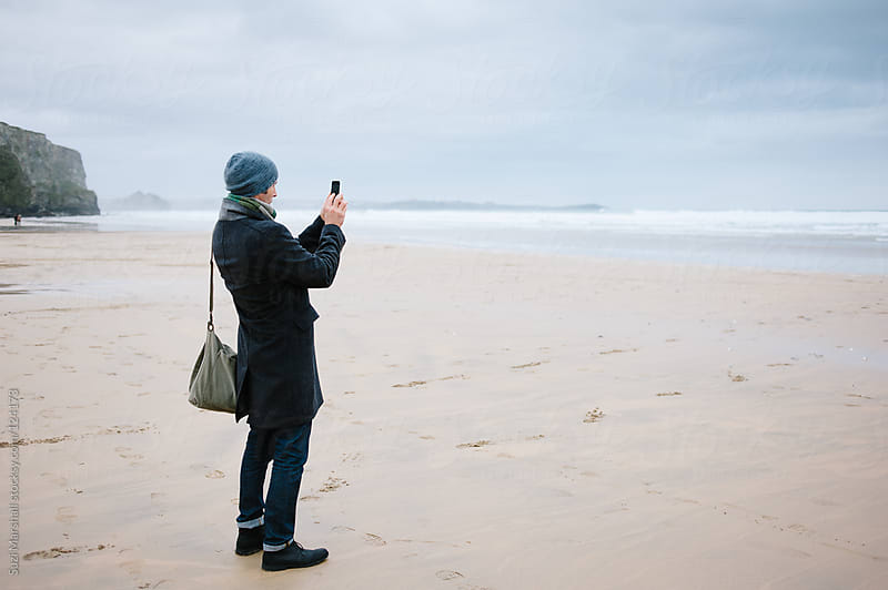 Man taking a picture of the sea with his phone  by Suzi Marshall for Stocksy United