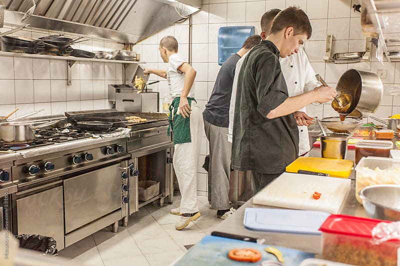 Professionals Working in the Restaurant Kitchen by Mosuno for Stocksy United