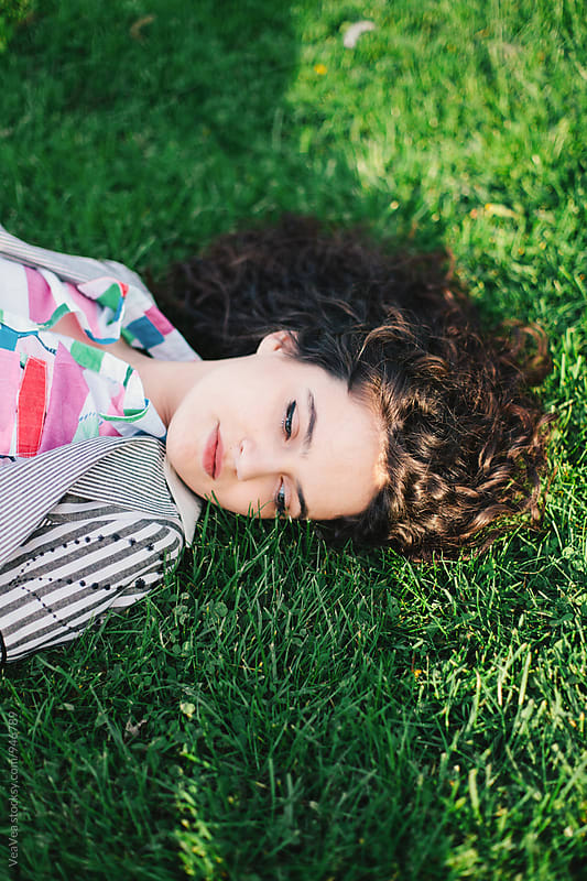 Woman lying on grass by Marija Mandic for Stocksy United