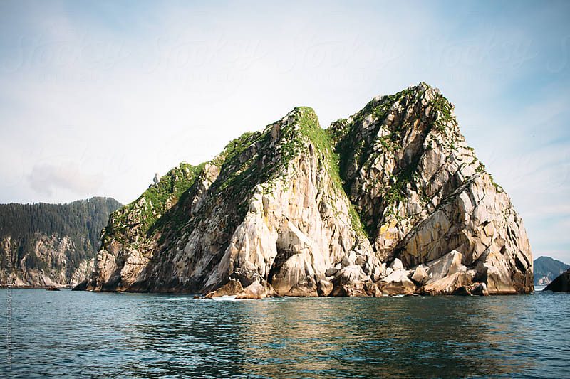 A Rocky Island Jutts Out Of The Ocean Water In Resurrection Bay by Luke Mattson for Stocksy United