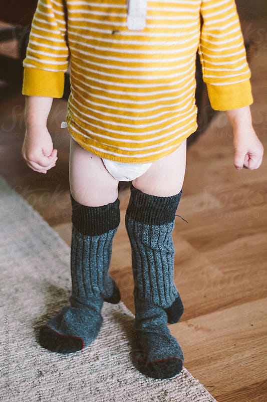 Toddler with big tall men's socks on. by Sarah Lalone for Stocksy United