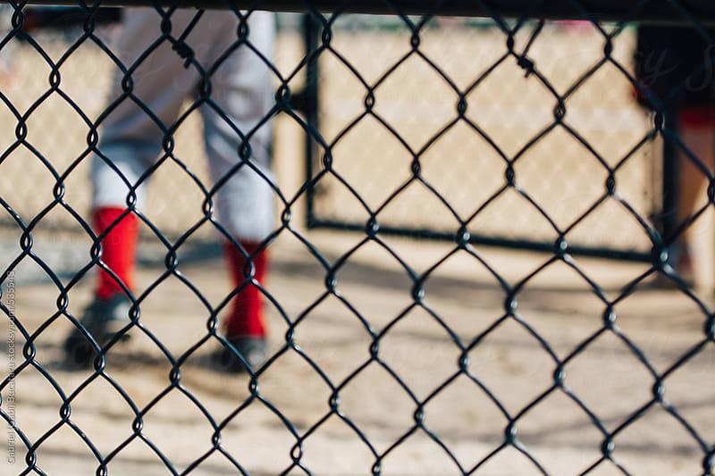 Junior baseball player legs through a wire fence by Gabriel (Gabi) Bucataru for Stocksy United