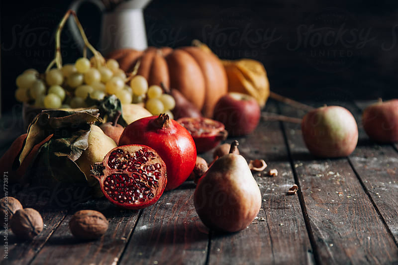 Different kind of fruits on a wooden table by Nataša Mandić for Stocksy United