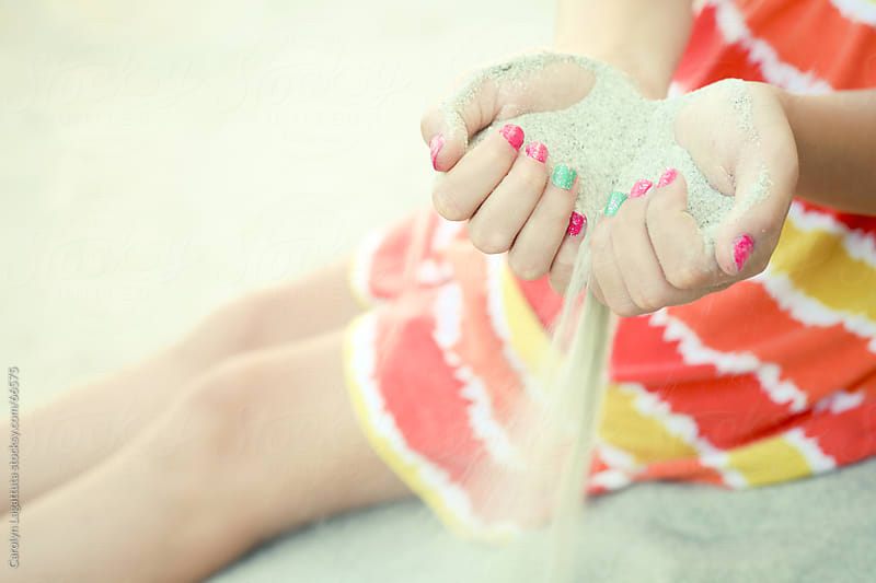 Sand slipping through a girls fingers at the beach by Carolyn Lagattuta for Stocksy United