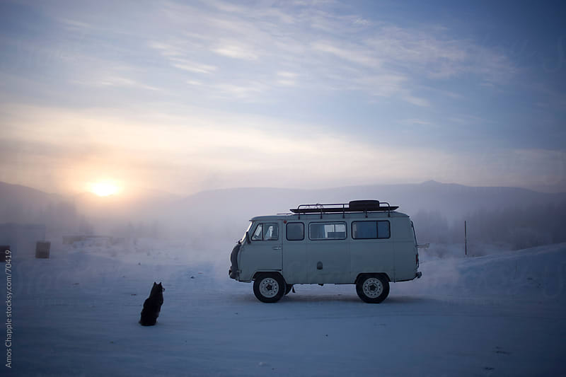 A dog waits next to a soviet-era van at a truck-stop in Siberia by Amos Chapple for Stocksy United