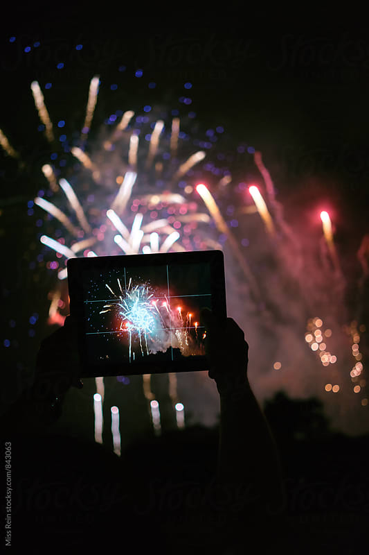 Watching Fireworks with a tablet at Holiday Celebration,shanghai,china by Miss Rein for Stocksy United