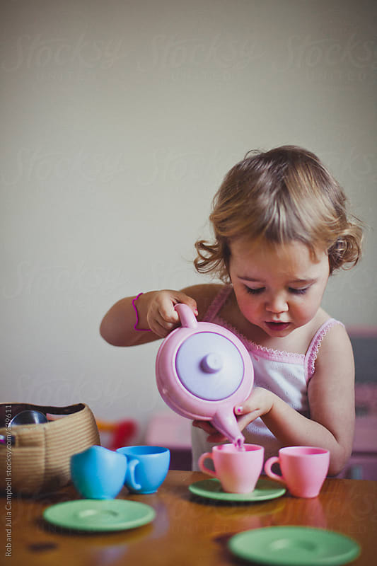 Cute toddler girl carefully pouring tea at a tea party by Rob and Julia Campbell for Stocksy United