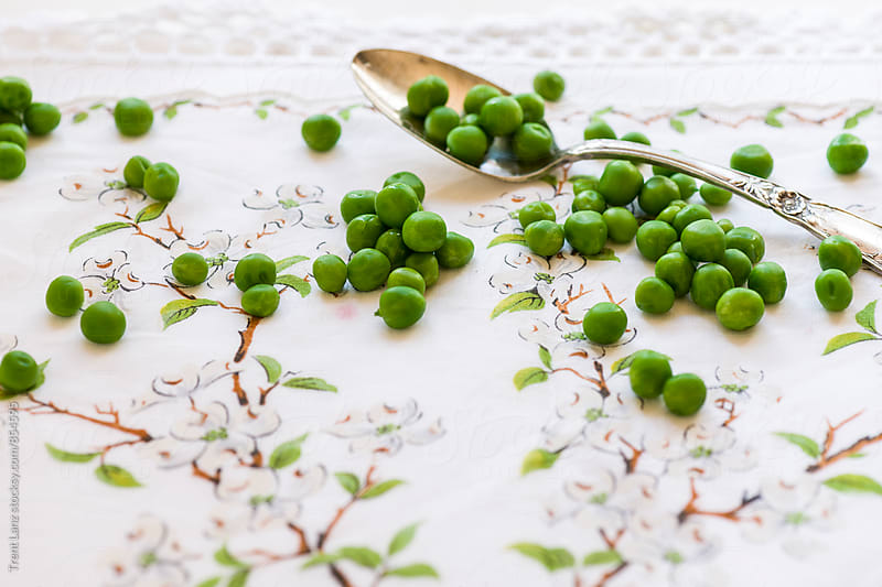 Organic fresh green peas on patterned linen napkin by Trent Lanz for Stocksy United