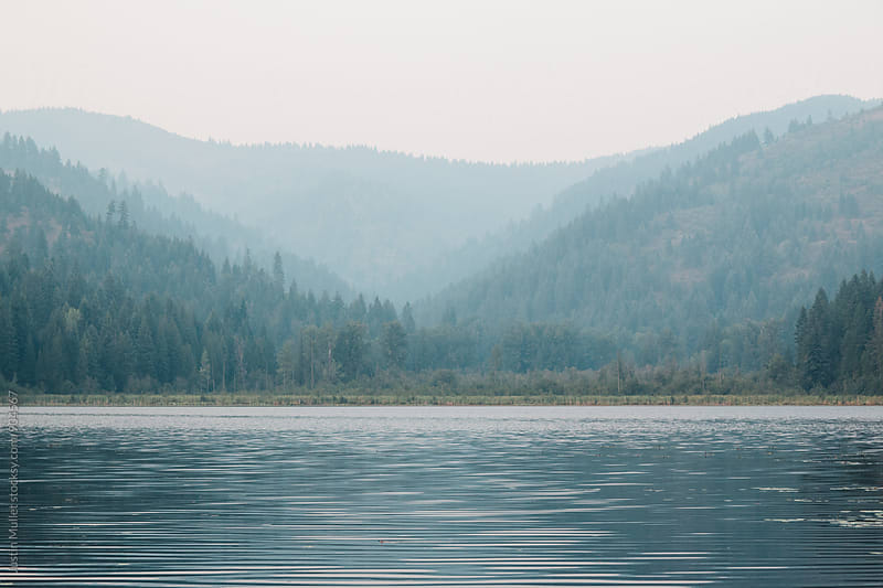 Wild fire smoke casting a blue hue over Freeman Lake, Idaho. by Justin Mullet for Stocksy United