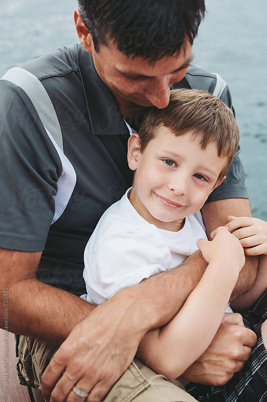Father and son smiling and cuddling at the lake by Rob and Julia Campbell for Stocksy United
