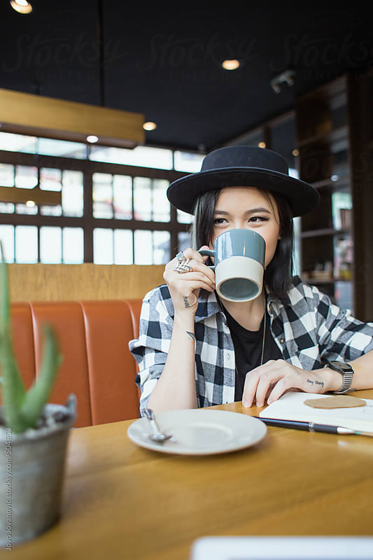Cute woman drinking her coffee in a coffee shop by Jovo Jovanovic for Stocksy United