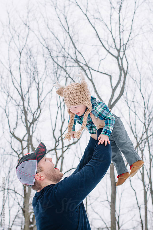 Father holds child  in the air outdoors by Jesse Morrow for Stocksy United