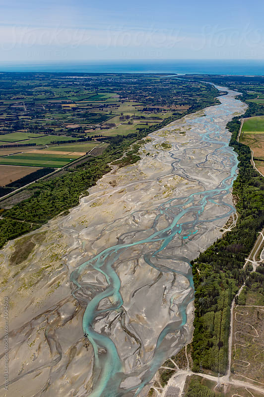 Aerial view of the Waimakariri River winding its way through the North Canterbury plains out to Pegasus Bay, New Zealand by Angela Lumsden for Stocksy United
