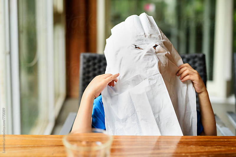 little kid wearing paper napkin on face like a halloween ghost by Lawren Lu for Stocksy United