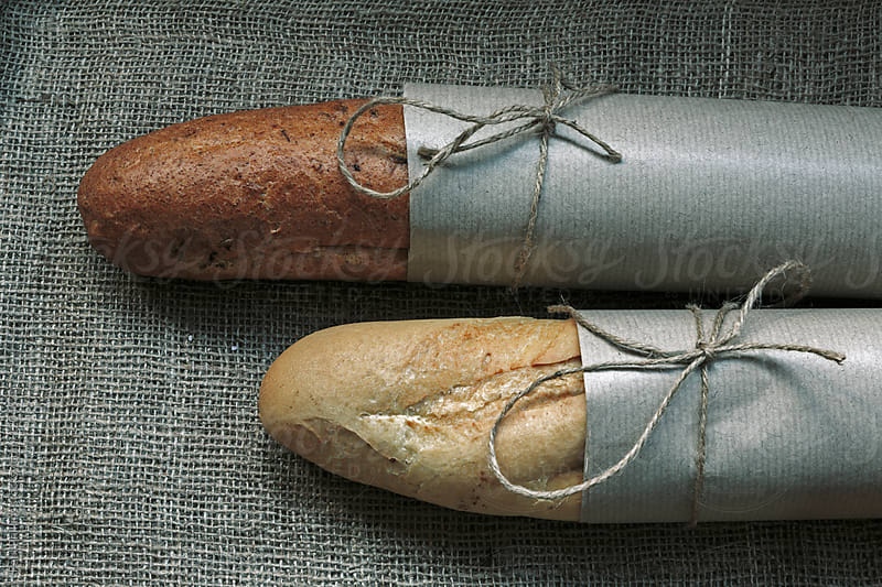 Two French Baguettes wrapped in paper lying on a hessian background by Paul Phillips for Stocksy United